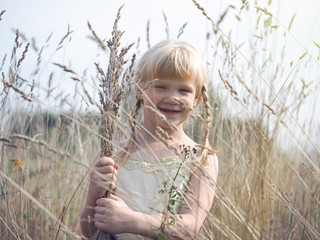 Incredibly happy child in the field. Emotional portrait of a child