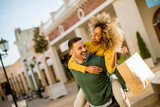 Young man holds young woman on his back , have fun and go to shopping - 231712243
