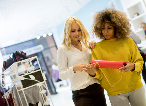 Leinwanddruck Bild Two young multiethnic women buying purse in the store