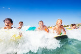 Happy teens riding the waves on body boards