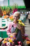 Senior woman sales flowers on local flower market - 231713492