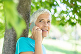 Portrait of sporty senior woman using mobile phone in the park - 231713665