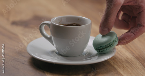 Poster man hand put light blue macaron on saucer with coffee cup