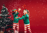 Little girls playing with the artificial snow flakes - 231716043