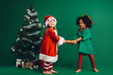 Little girls standing near a christmas tree holding a toy - 231716801