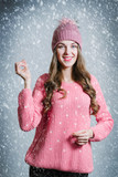 Pretty young woman in hat and warm sweter holding a snowflake over the snow falling background
