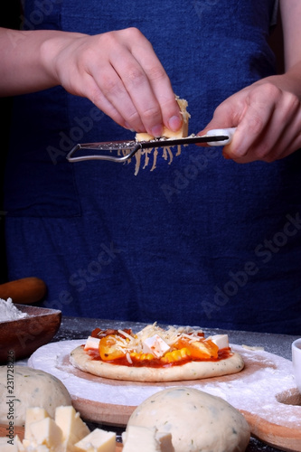Wall mural Process of making pizza. The cook wearing a blue apron is grating cheese