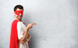 Superhero man with mask and red cape pointing finger to the side and presenting a product in lateral position on textured grey background