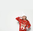 Leinwandbild Motiv Cute little girl in Christmas sweater and knitted hat on white background. Space for text