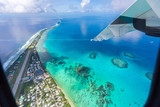 Tuvalu lagoon under wing of an airplane. Aerial view of Funafuti atoll and the airstrip of International airport in Vaiaku. Fongafale motu. Island nation in Polynesia, South Pacific Ocean, Oceania. - 231742054