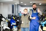 happy male worker assisting female customer in repairing motorcycle in workshop