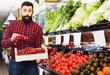 Leinwanddruck Bild - Seller showing fresh tomatoes in grocery shop