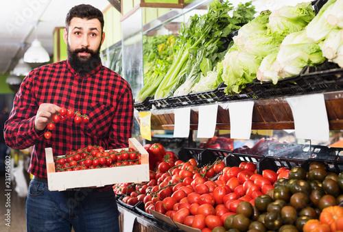 Leinwanddruck Bild Seller showing fresh tomatoes in grocery shop