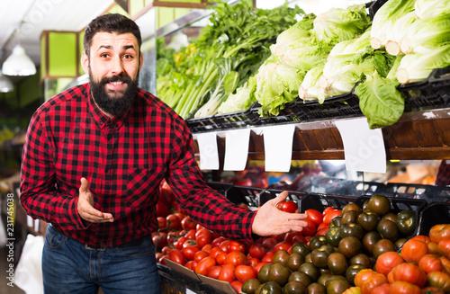 Leinwanddruck Bild Smiling man seller offering tomatoes in shop