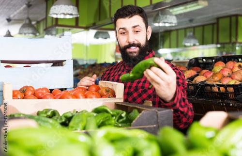 Leinwanddruck Bild Man seller showing sweet peppers in grocery store