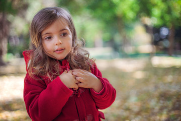 Beautiful little girl sitting in fallen leaves at autumn park