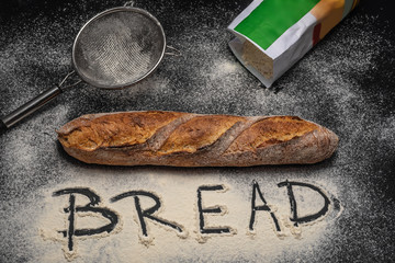 Bread and flour. Freshly backed baguette on black background