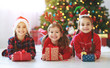 Leinwanddruck Bild - happy children girls with christmas gifts near tree in  morning