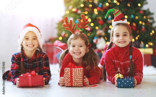 Leinwanddruck Bild happy children girls with christmas gifts near tree in  morning