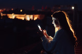 Young girl sits at night on the roof of a house. Beautiful evening - 231758896