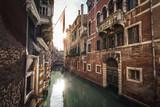 Kanal in Venedig mit Häusern und untergehender Sonne - 231760091