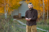 a bearded Russian man holds a handful of garlic in his hands, ready for planting on the beds. autumn, in the background birch with fiery yellow foliage - 231762676