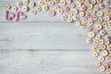 Wooden light spring-summer background with daisies and hearts
