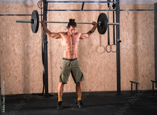 Wall mural Strong young man lifting bar with weight in the gym