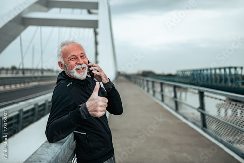 Poster Portrait of a senior sportsman talking on the mobile phone and showing thumbs-up in the city.