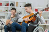 friends playing music, one in wheelchair - 231782010
