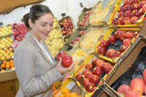 pretty woman buying fresh fruits and vegetables at food-store - 231782462
