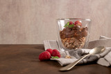 Glass cups of chocolate and chestnuts mousse with roasted almonds and oats decorated with raspberry and mint leaves - 231783280