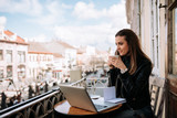 Cute girl drinking a cup of coffee on the balcony while studying. - 231783447