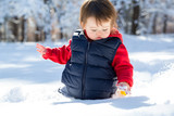 Toddler boy playing in the snow on a winter day - 231793438