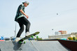 Full length portrait of contemporary young man doing longboard stunts on ramp in skateboarding park, copy space