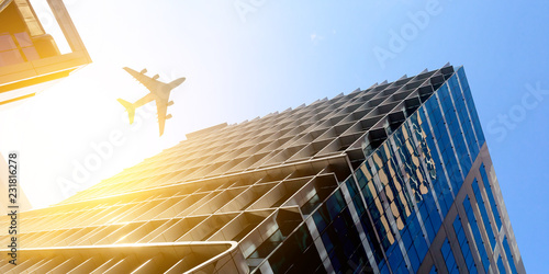 Foto Murales Airplane above business city
