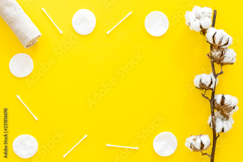 Leinwanddruck Bild Products made of cotton. Bath accessories. Towels, cotton pads and swabs near dry cotton flowers on yellow background top view copy space frame