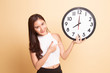 Young Asian woman point to a clock.