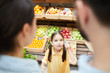 Cheerful excited girl with pony tails showing index finger while having idea in food store and offering it to parents