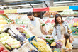 Cheerful beautiful young family in casual clothing walking over farmers market and buying food for dinner together