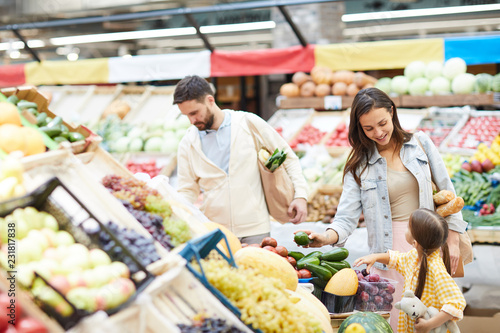 Foto Murales Cheerful beautiful young family in casual clothing walking over farmers market and buying food for dinner together