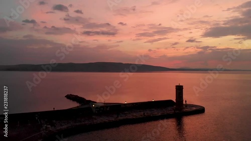 Ascending drone shoot of a light house after a warm sunset