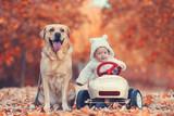 kleiner Junge mit Hund und Tretauto - 231822606