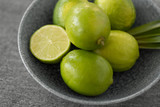 food, healthy eating and vegetarian concept - close up of limes in bowl on slate table top