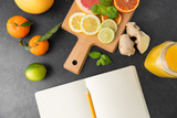 food, healthy eating and vegetarian concept - close up of citrus fruits, wooden cutting board and notebook on slate table top
