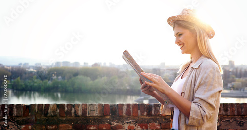 Foto Murales Tourist woman holding travelers map to travel to destination