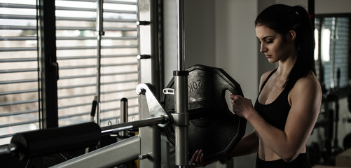 Woman adding weight on a bar as she workout in fitness gym © Samo Trebizan