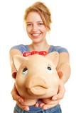 Junge Frau hält Sparbüchse oder Sparschwein - 231844044
