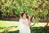Beautiful brunette bride with bouquet outdoor. Happy bride outdoors.