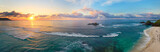 Panoramic view of tropical beach with surfers at sunset.